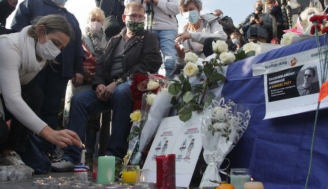 Άνθρωποι αφήνουν λουλούδια στο σημείο δολοφονίας του καθηγητή Σαμιέλ Πατί
