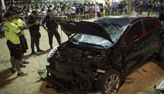 Police officers stand next to the a car that has driven into the crowded seaside boardwalk along Copacabana beach in Rio de Janeiro, Brazil, Thursday, Jan. 18, 2018. Military police said on Twitter that at least 11 people were injured and that the driver has been taken into custody. (AP Photo/Silvia Izquierdo)