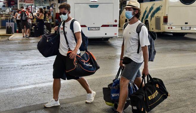 Νεαροί άνδρες με μάσκα στα ΚΤΕΛ Κηφισού.