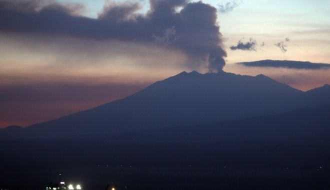 A ferry boat crosses Bali Strait to carry Indonesians to Ketapang port, East Java, from Gilimanuk port, West Bali, Indonesia as Mount Raung spews volcanic smoke Sunday, July 12, 2015. Ash spewing from the volcano sparked chaos for holidaymakers as airports closed and international airlines canceled flights to tourist hotspot Bali, stranding thousands. (AP Photo/Firdia Lisnawati)
