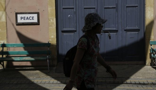 """A woman from Asia in silhouette walks at Ladras street as a sign on a wall reads """"Peace"""" next to the crossing point leading to the Turkish Cypriot breakaway north in the divided capital, Nicosia, Cyprus, Thursday, July 6, 2017. U.N. Secretary-General Antonio Guterres is attending Cyprus peace talks in Switzerland in an effort to bridge differences between the rival sides. Guterres' appearance is his second during the nine days of negotiations, which have so far failed to achieve much progress in reunifying the ethnically divided Mediterranean island nation as a federation. (AP Photo/Petros Karadjias)"""