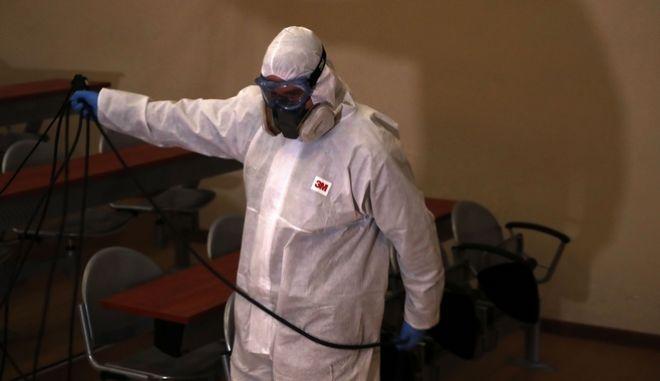 Έλληνας εργάτης φοράει την προστατευτική στολή για τον κορονοϊό