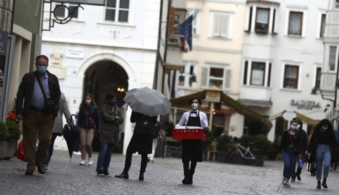 People wear face masks to protect against the coronavirus in the streets of Bolzano, known in German as Bozen, Italy, Monday, May 11, 2020. The northern Italian province of South Tyrol is moving ahead of policies by the central government, reopening restaurants and shops closed during the coronavirus crisis earlier than planned by Rome. (AP Photo/Matthias Schrader)
