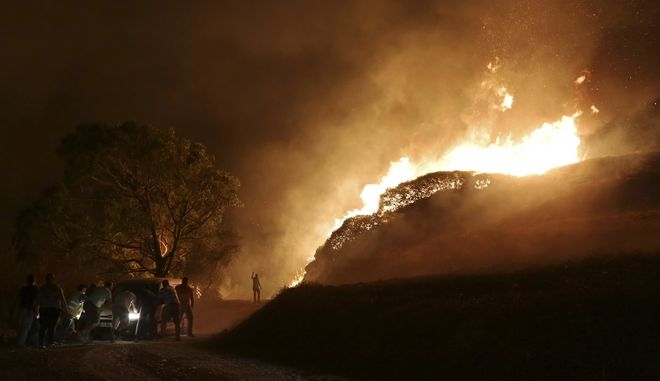 People push a van that got stuck bringing water for volunteers to fight a wild fire raging near houses in the outskirts of Obidos, Portugal, in the early hours of Monday, Oct. 16 2017. Wildfires in Portugal killed at least 27 people, injured dozens more and left an unconfirmed number of missing in the country's second such tragedy in four months, officials said Monday. (AP Photo/Armando Franca)