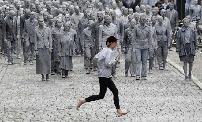 A woman crosses the street in front of the approaching performance '1000 GESTALTEN' with hundreds of people painted like clay figures moving slowly and silently through the streets of Hamburg to protest against the G-20 summit in Hamburg, northern Germany, Wednesday, July 5, 2017. The leaders of the group of 20 meet July 7 and 8. (AP Photo/Matthias Schrader)