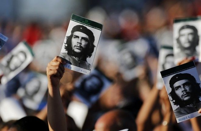 People wave pictures at an event paying tribute to Cuban Revolution hero Ernesto Che Guevara marking the 50th anniversary of his death in Santa Clara, Cuba, Sunday, Oct. 8, 2017. (AP Photo/Desmond Boylan)