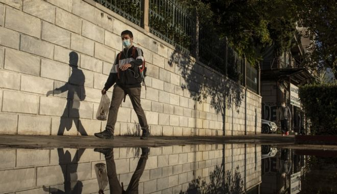 A man wearing a face mask to prevent the spread of COVID-19 is reflected in a puddle as he walks in central Athens, Thursday, Oct. 29, 2020. Greece is seeing a record-breaking jump in the number of confirmed coronavirus cases for the second consecutive day, with 1,547 new cases announced Wednesday, Oct 28, and 10 new deaths. (AP Photo/Petros Giannakouris)