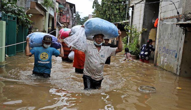 Πολίτες στην Ινδονησία κουβαλούν τα υπάρχοντά τους καθώς περνούν μέσα από το νερό σε πλημμυρισμένη γειτονιά  στην Τζακάρτα της Ινδονησίας, 19 Φεβρουαρίου 2021.
