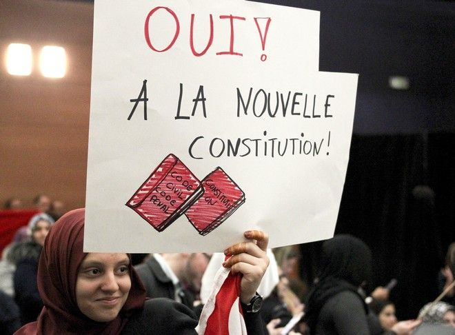 A woman holds a banner which reads,