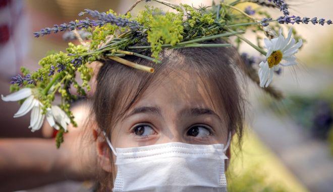 Ένα κορίτσι φορά μάσκα στην εποχή του κορονοϊού στη Ρουμανία
