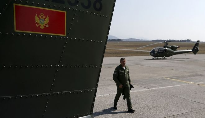 A crew member passes by a Montenegrin army helicopter at Golubovci airport, near Podgorica, Montenegro, Wednesday, March 15, 2017. Aspiring NATO member Montenegro is hardly a formidable military force, the tiny country's four military jets are up for sale and its two operational warships hardly ever leave their home port, but  Montenegro has found itself in the middle of a major row between the West and Moscow.