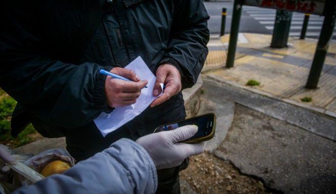 Πολίτης δείχνει το κινητό του σε αστυνομικό