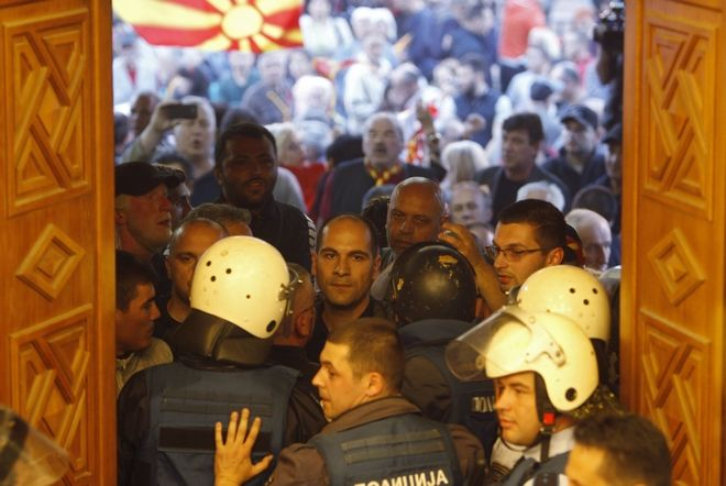 Police try to block protestors as they enter into the parliament building in Skopje, Macedonia, Thursday, April 27, 2017. Scores of protesters have broken through a police cordon and entered Macedonian parliament to protest the election of a new speaker despite a months-long deadlock in talks to form a new government. (AP Photo/Boris Grdanoski)