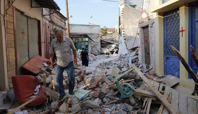 Κάτοικοι του χωριού Βρίσα προσπαθούν να μαζέψουν ό,τι μπορούν μέσα στα συντρίμμια των σπιτιών μετά τον σεισμό των 6,1 Ρίχτερ που έπληξε την περιοχή