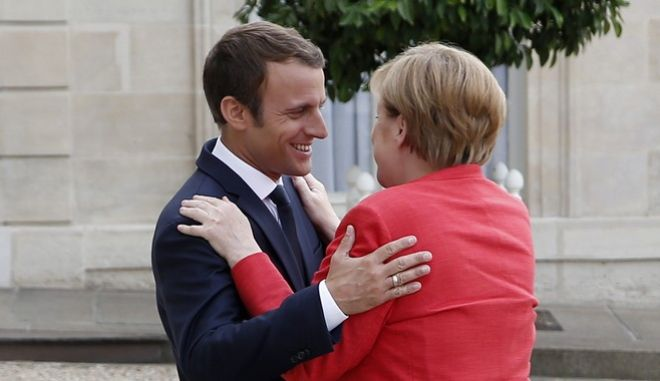 French President Emmanuel Macron welcomes German Chancellor Angela Merkel at the Elysee Palace in Paris, Monday, Aug.28, 2017. The leaders of France, Germany, Italy and Spain are meeting Monday with counterparts from Libya, Niger and Chad to discuss ways to curb illegal migration across the Mediterranean Sea to European shores (AP Photo/Thibault Camus)