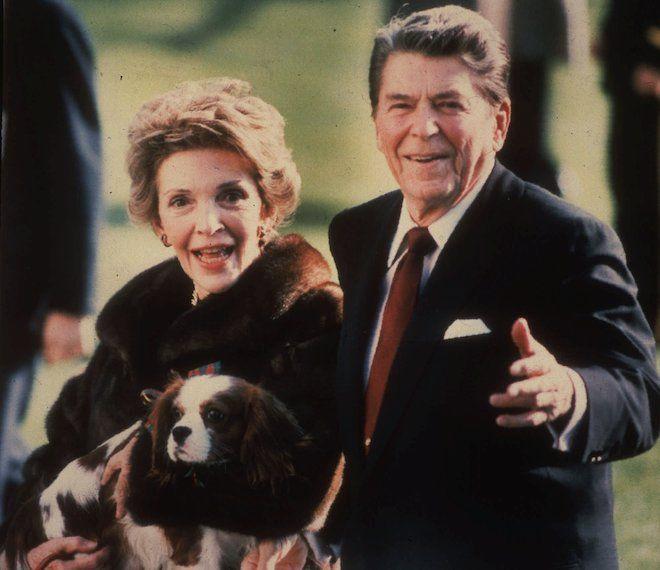 Αυτή η φωτογραφία αρχείου του Δεκεμβρίου του 1986 δείχνει την πρώτη κυρία Νάνσι Ρέιγκαν να κρατάει το κατοικίδιο ζώο τους Rex, ένα σπάνιελ Κινγκ Τσαρλς, καθώς αυτή και ο Πρόεδρος Ρέιγκαν περπατούν στο γκαζόν του Λευκού Οίκου.