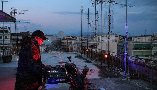 Ο dj Γιάννης Καλλιμάνης, έπαιξε μουσική σε ταράτσα πολυκατοικίας στην Λάρισα για τους συμπολίτες του που βρίσκονται στα σπίτια τους στα πλαίσια της προσπάθειας εξάπλωσης του κορονοϊού, το απόγευμα της Τετάρτης 18 Μαρτίου 2020. (EUROKINISSI/ΛΕΩΝΙΔΑΣ ΤΖΕΚΑΣ)