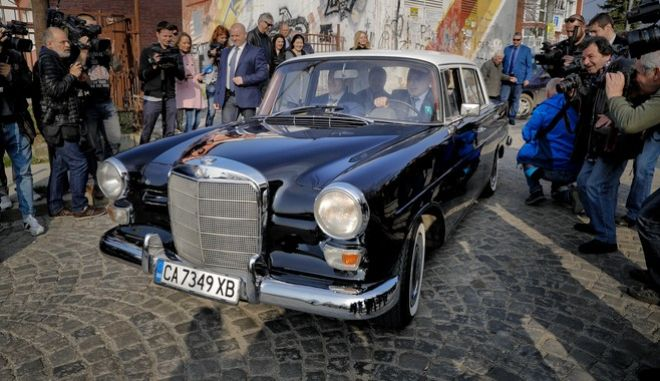 Bulgarian ex-Premier Boiko Borisov, leader of the center-right GERB party, drives a vintage Mercedes as he leaves a voting station, in Sofia, Bulgaria, Sunday, March 26, 2017. Bulgarians are heading to the polls for the third time in four years in a snap vote that could tilt the European Union's poorest member country closer to Russia as surveys put the center-right GERB party neck-and-neck with the Socialist Party. (AP Photo/Vadim Ghirda)