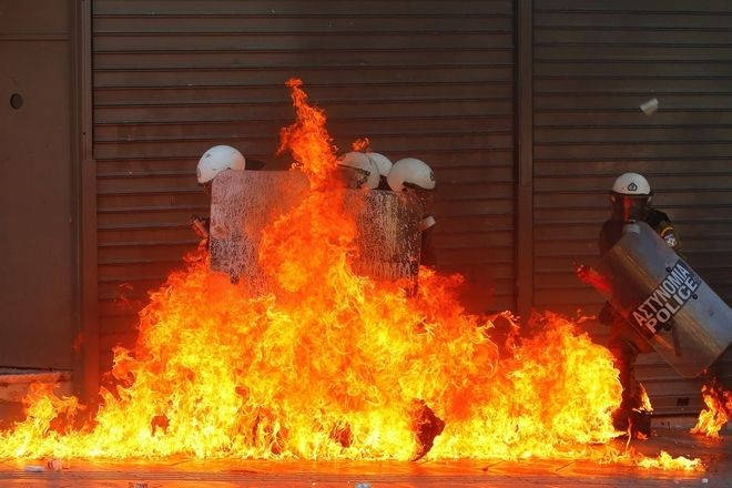 A group of riot policemen is engulfed in flames after protesters threw petrol bombs in Athens' Syntagma square during a 24-hour labour strike.