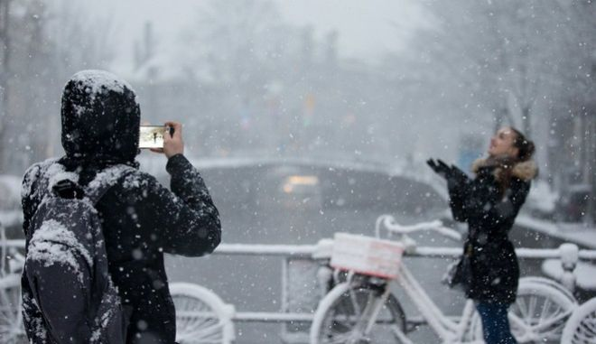 A tourist takes a picture of his girlfriend as snow covers the city of Amsterdam, Netherlands, Monday, Dec. 11, 2017. (AP Photo/Peter Dejong)