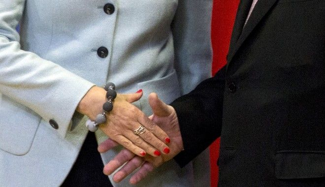 British Prime Minister Theresa May, left, shakes hands with European Commission President Jean-Claude Juncker, right, prior to a meeting at EU headquarters in Brussels on Friday, Dec. 8, 2017. British Prime Minister Theresa May, met with European Commission President Jean-Claude Juncker early Friday morning following crucial overnight talks on the issue of the Irish border.(AP Photo/Virginia Mayo)