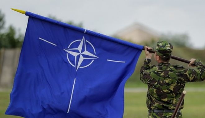 """A Romanian serviceman furls the NATO flag after Britain's Defense Minister Michael Fallon's visit at the Mihail Kogalniceanu air base in Romania, Wednesday, June 14, 2017.  Britain's defense minister praised Romanian and British pilots for protecting the Black Sea region from """"the persistent threat of Russian aggression,"""" saying that Britain remains committed to NATO and the European security.(AP Photo/Vadim Ghirda)"""