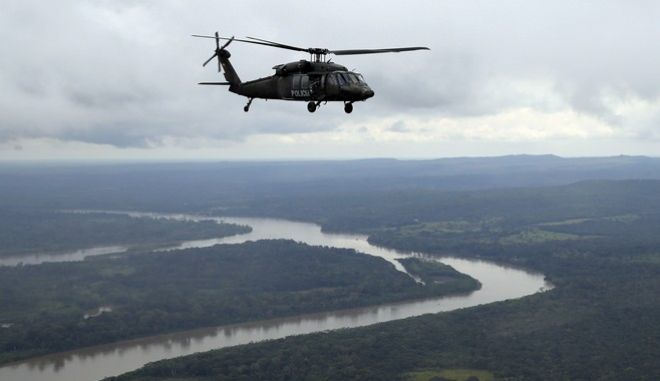 An anti-narcotics helicopter flies over San Jose del Guaviare, Colombia, Tuesday, Aug. 2, 2016. Colombian police destroyed about 104 illegal cocaine labs in anti-narcotics operations during the las five days. (AP Photo/Fernando Vergara)