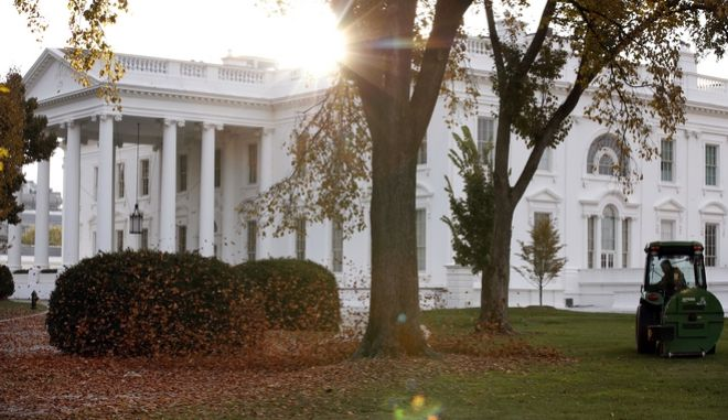 A tractor uses a leaf blower to gather the fallen leaves on the North Lawn as the sun rises over the White House, Saturday, Nov. 18, 2017, in Washington. (AP Photo/Alex Brandon)