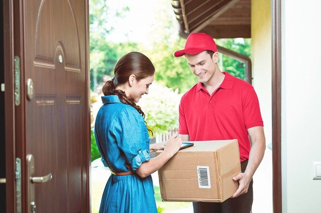 Delivery man standing at the door of the house and carrying parcels for young woman. Woman signing.