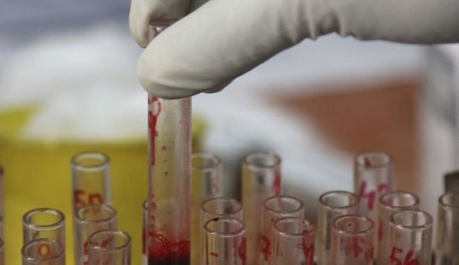 An Indian pathologist preserves blood samples collected from patients suffering from fever for analytical tests at Government Osmania General Hospital in Hyderabad, India, Saturday, Sept. 19, 2015. India's capital struggles with its worst outbreak of the dengue fever in five years. Outbreaks of the mosquito-borne disease are reported every year after the monsoon season that runs from June to September. (AP Photo/Mahesh Kumar A.)