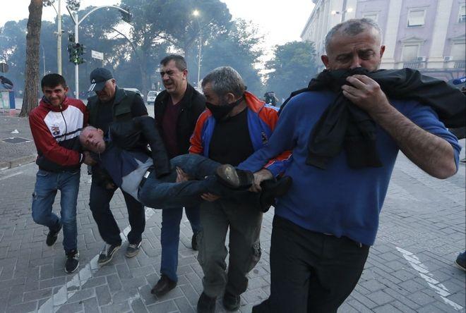 Διαδηλωτές μεταφέρουν έναν άνδρα που έχει χάσει τις αισθήσεις του