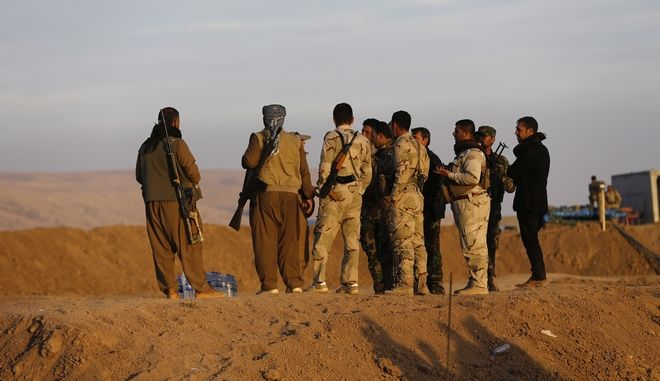 In this photo taken on Thursday Nov. 17, 2016, Kurdish Peshmerga fighters stand on a sand barrier created by Kurdish forces to demarcate their border, in the Nineveh plain, northeast of Mosul, Iraq. The sand berms and trenches snake across northern Iraq all the way to Syria, alongside newly paved roads and sprawling checkpoints decked with Kurdish flags, in what increasingly resembles an international border. The boundary takes in lands claimed by the Kurds and the Baghdad government, and could ignite a new conflict once the Islamic State group is defeated. (AP Photo/Hussein Malla)