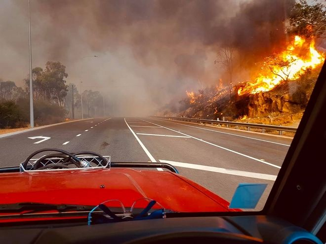 In this photo provided by Department of Fire and Emergency Services, flames approach a road at Wooroloo, near Perth, Australia, Monday, Feb. 1, 2021. An out-of-control wildfire burning northeast of the Australian west coast city of Perth has destroyed an estimated 30 homes and was threatening more Tuesday, with many locals across the region told it is too late to leave. (Greg Bell/DFES via AP)