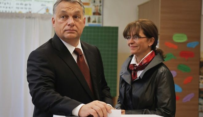 Hungarian Prime Minister Viktor Orban casts his vote in the referendum as his wife Aniko Levai stands by in Budapest, Hungary, Sunday, Oct. 2, 2016. Hungarians vote in a referendum which Prime Minister Viktor Orban hopes will give his government the popular support it seeks to oppose any future plans by the European Union to resettle asylum seekers among its member states. (AP Photo/Vadim Ghirda)
