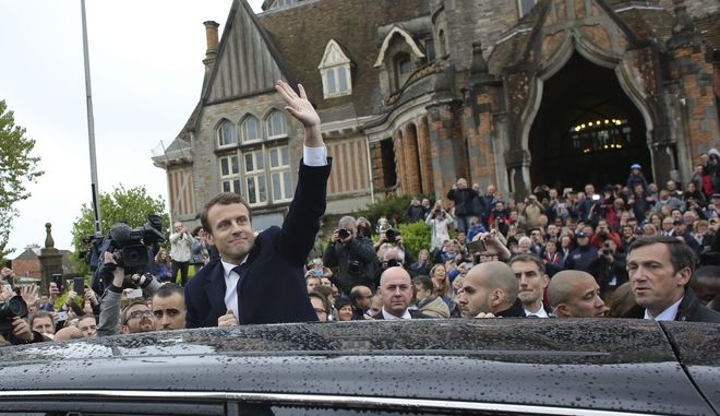 French independent centrist presidential candidate Emmanuel Macron, center, waves as he leaves the polling station after casting his ballot in the presidential runoff election in Le Touquet, France, Sunday, May 7, 2017. Voters across France are choosing a new president in an unusually tense and important election that could decide Europe's future, making a stark choice between pro-business progressive candidate Emmanuel Macron and far-right populist Marine Le Pen. (AP Photo/Thibault Camus)