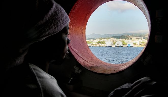 FILE - In this Saturday June 25, 2016 file photo, a woman looks out of the porthole from aboard the 'Aquarius' rescue vessel after arriving in Sicily, Italy with more than 600 migrants aboard the ship rescued by SOS Mediterranee and the medical aid group Medecins Sans Frontieres (MSF). By trying to prevent migrants from taking the dangerous sea journey across the Mediterranean, they are dooming them to prolonged abuse in Libya at the hands of authorities and the countrys many militias, rights groups warn. (AP Photo/Bram Janssen, File)