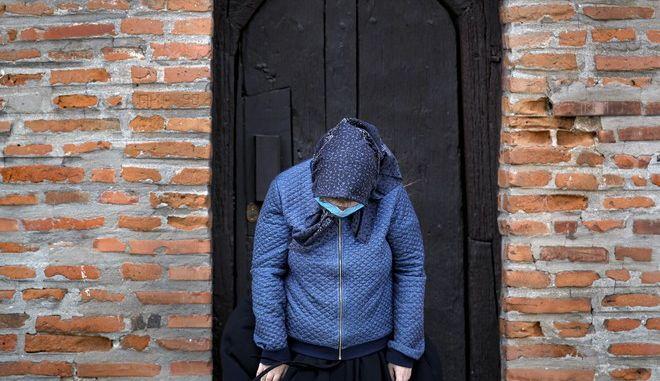 Γυναίκα που φοράει προστατευτική μάσκα για τον κορονοϊό κοιτάζει στο έδαφος