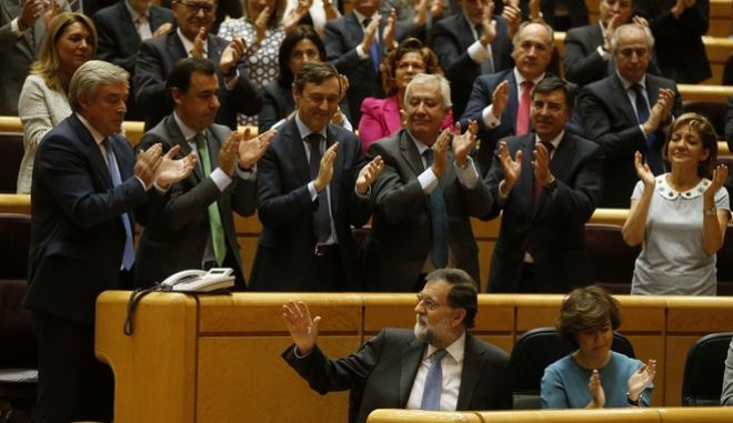 Spain's Prime Minister Mariano Rajoy acknowledges applause from the chamber after a speech at the Senate in Madrid, Spain, Friday, Oct. 27, 2017. Rajoy has appealed to the country's Senate to grant special constitutional measures that would allow the central government to take control of Catalonia's autonomous powers to try to halt the region's independence bid. (AP Photo/Paul White)