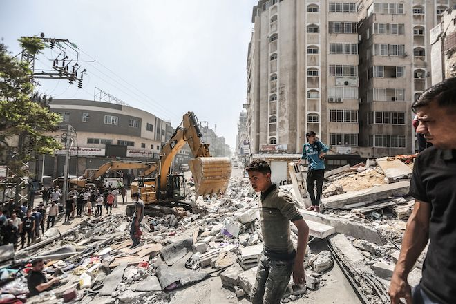People clear debris after Israeli airstrike destroyed the residential tower in Gaza city. 11 days of Israels intense aerial and ground bombardments has caused a huge impact on peoples lives in Gaza - people lost their family members, their homes and livelihoods and have suffered long-lasting physical and psychological injuries.