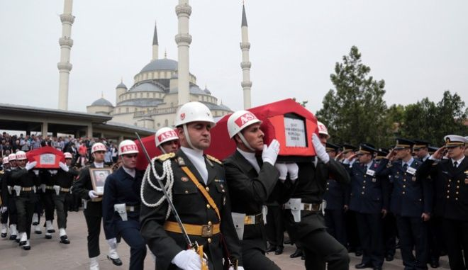 Turkish army commanders salute during the funeral ceremony for pilot Lt. Burak Abikebahsi and army officer Mekan Sahin at the Kocatepe Mosque in Ankara, Turkey, Saturday, May 14, 2016. Eight military personnel have died in clashes with  militants of the outlawed Kurdistan Workers Party, or PKK, in Hakkari province at the border with Iraq on Friday, statement from the military said.(AP Photo/Burhan Ozbilici)