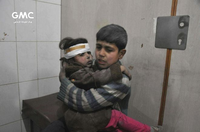 This photo released on Wednesday Feb. 21, 2018 provided by the Syrian anti-government activist group Ghouta Media Center, which has been authenticated based on its contents and other AP reporting, shows two Syrian kids who were wounded during airstrikes and shelling by Syrian government forces, sit at a makeshift hospital, in Ghouta, suburb of Damascus, Syria. New airstrikes and shelling on the besieged, rebel-held suburbs of the Syrian capital killed at least 10 people on Wednesday, a rescue organization and a monitoring group said. (Ghouta Media Center via AP)
