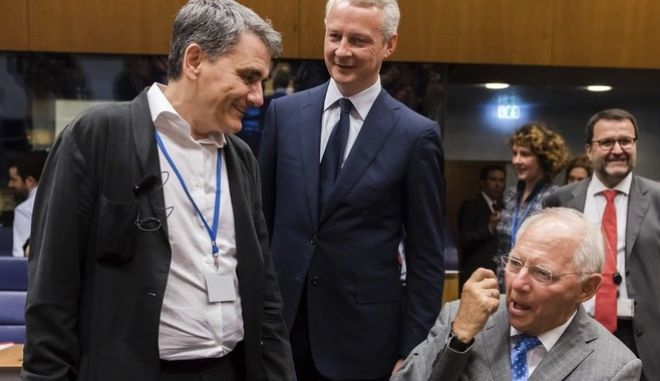 German Finance Minister Wolfgang Schaeuble, left, speaks with Greek Finance Minister Euclid Tsakalotos, right, and French Finance Minister Bruno Le Maire during a meeting of eurogroup finance ministers at the European Council building in Luxembourg on Thursday, June 15, 2017. Eurogroup finance ministers met on Thursday to review the bailout program for Greece. (AP Photo/Geert Vanden Wijngaert)
