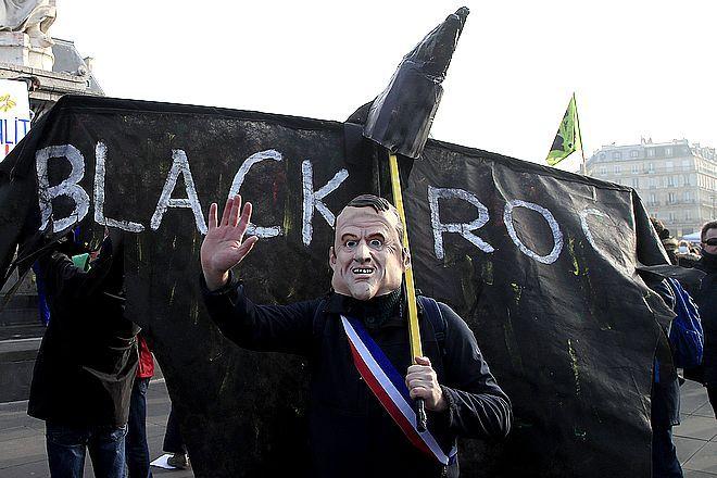Διαδηλωτής με μάσκα Μακρόν