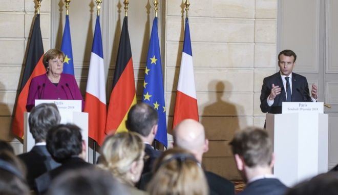 France's President Emmanuel Macron, right, and German Chancellor Angela Merkel, left, give a press conference, prior to a meeting, at the Elysee Palace, in Paris, Friday, Jan. 19, 2018. Meeting Friday with French President Macron in Paris, Merkel said she hopes the party congress will give the green light for us to enter coalition negotiations.  (Christophe Petit Tesson, Pool via AP)
