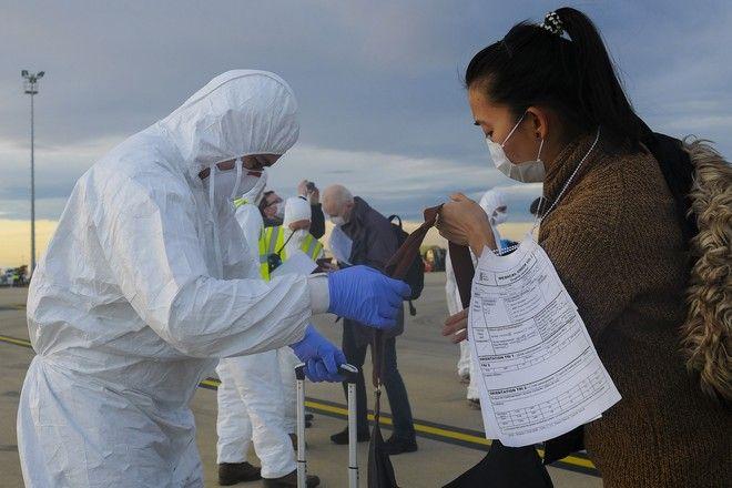 Επιβάτες φορούν μάσκες σε αεροδρόμιο