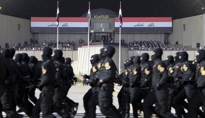 In this photo provided by the Iraqi Prime Minister's Media Office, troops march in a military parade in Baghdad, Iraq, Saturday July 15, 2017, in front of Prime Minister Haider al-Abadi, background center, during victory celebrations over Islamic State militants. Iraqi forces recaptured Mosul after the city was held for around three years by the IS. (Iraqi Prime Minister's Media Office via AP)