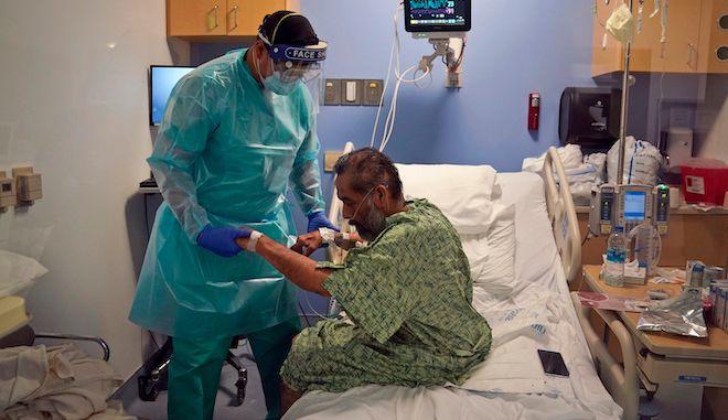 Φυσιοθεραπευτής βοηθά έναν ασθενή με COVID-19 να καθίσει στο κρεβάτι του στο νοσοκομείο St. Joseph στην Καλιφόρνια, 7 Ιανουαρίου, 2021.
