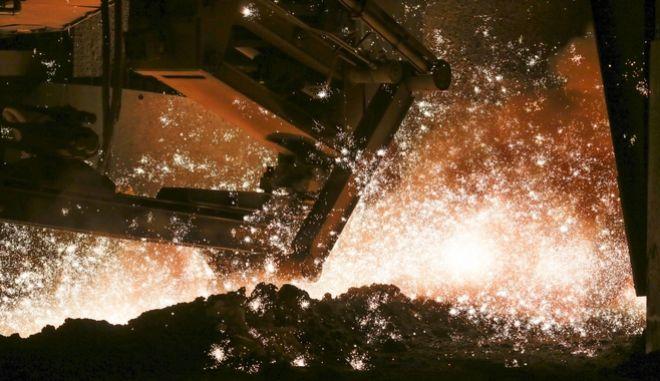 Υγρός σίδηρος εξέρχεται από τους φούρνους στις εγκαταστάσεις επεξεργασίας μετάλλου στο Σάλζγκιτερ της Γερμανίας