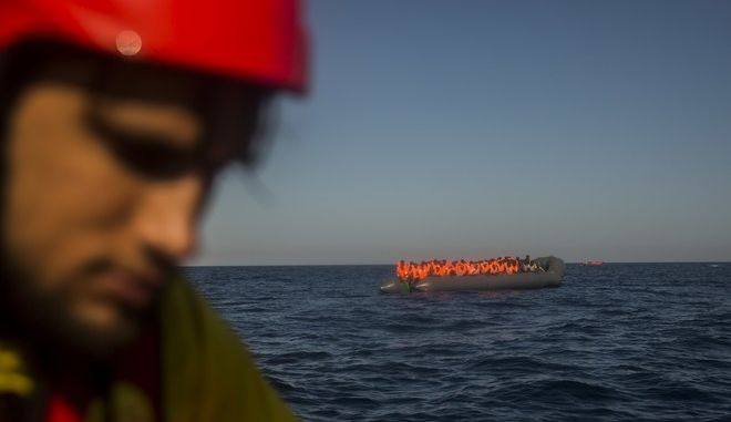 Member of the Spanish NGO Proactiva Open Arms assist refugees and migrants, from different African countries that left Libya aboard 2 overcrowded rubber boats, about 20 miles North of Sabratha, Libya, Saturday, March 4, 2017. A rescue ship belonging to a Spanish NGO has saved 250 migrants in danger of capsizing near the Libyan coast on Saturday. Proactiva Open Arms spokesperson Laura Lanuza says that the NGO's boat rescued the African migrants from two small rubber vessels that were at risk of being overwhelmed by the sea. (AP Photo/Santi Palacios)