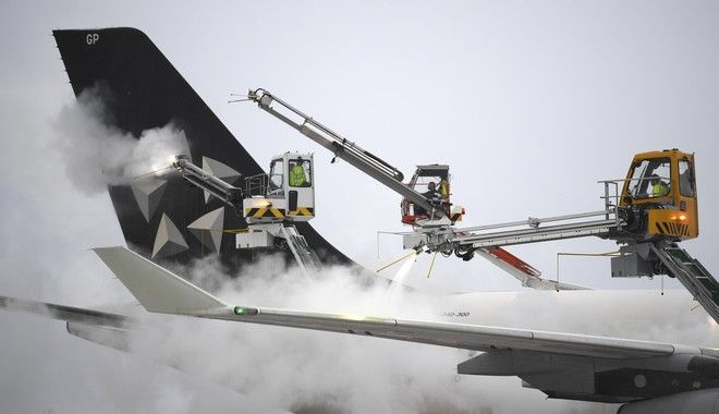Workers deice a plane of the Star Alliance at the airport in Frankfurt, Germany, Sunday, Dec. 10, 2017. Heavy snowfalls and low temperatures led flight delays and cancellations. (Arne Deder/dpa via AP)